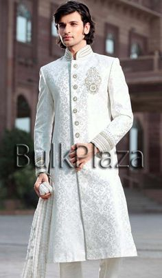 Debonair off white color jacquard sherwani with sparkling diamantes, stones, jari, pearls, cutdana, jardozy work on high neck collar, cuffs, chest butta and buttons on front panel are making it outstanding creation. Self designed motifs all over the base giving it a rich ethnic texture. Attractive matching churidar is making the outfit more attractive. It can be selected for special day.