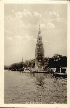 1940's. Montelbaanstoren at the Oude Schans in Amsterdam. On the left the tower of the Zuiderkerk and on the right the Oude Waal. The original tower was built in 1516 for the purpose of defending the city. The top half, designed by architect Hendrick de Keyser, was extended to its current, decorative form in 1606. Photo HWA. #amsterdam #1940 #Montelbaanstoren