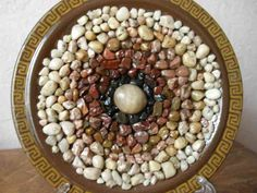 """Собрать различные камушки. Промыть все собранные """"уникальные"""" экземплярчики. Рассортировать их по цвету, чем контрасней подберете, тем легче оформлять узор. Взять любую тарелку и фантазировать с узором,  темные камни у центра и светлее по краям Затем тарелку протереть  водкой,  И начинать клеить с центра тарелки.Клей лучше наносить на сам камень, тогда получается аккуратней. По краю тарелки можно нанести кисточками любой орнамент. Дать просохнуть клею 1 сутки и покрыть все бесцветным лаком…"""