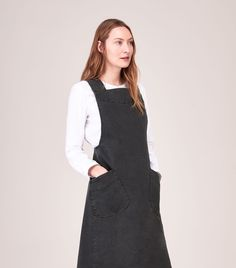 Apron dress in weighty, washed cotton twill. Slanted patch pockets. Wide straps, crossing over at back. Large, asymmetric pleat at back. Concealed side zip.