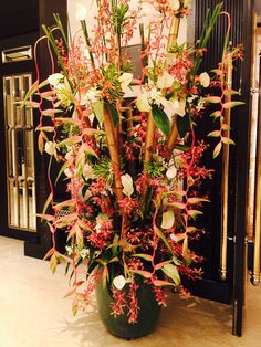 Entrance pot arrangements with gold tinted bamboo sticks- hangng halyconias, white anthuriums, anne black orchids and song of india leaves form the most part of this stunning piece