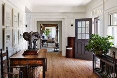 Greeting visitors in the entrance hall is a bronze elephant sculpture atop a 19th-century English country table from Yew Tree House Antiques; on the wall is a series of Richard Diebenkorn lithographs.