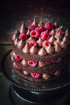 Easy chocolate cake that is moist and made with pantry ingredients. It is frosted with a rich chocolate fudge frosting and fresh raspberries to decorate | by sugaretal.com