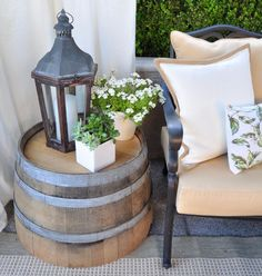 Front porch decor: half-whiskey barrel table, Lantern, flowers pulled, curtain = inviting.