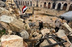 A member of forces loyal to Syria's President Bashar al-Assad attempts to erect the Syrian national flag inside the Umayyad mosque, in the government-controlled area of Aleppo, Syria. Omar Sanadiki / Reuters
