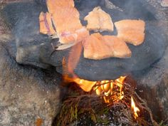 No trees in Nunavut so camp fires are made with Heather. Cooking Arctic Char. Heather tea is made by placing the kettle on the stone and the aroma of the heather flavours the tea.  Photo by Michael Illuitok :)