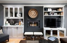 After: A gorgeous ethanol fireplace was installed beside the TV. It was finished with more custom cabinetry housing a bar. The cabinets feature open shelving to show off pretty pieces, and antique mirrored glass doors hide less-looky items.