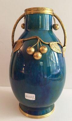 SEVRES Vase en porcelaine bleu-vert et monture en bronze doré à décor de cerises Cachet de la manufacture sous la base H: 25,5 cm (Trois fêles au niveau du col) - Millon & Associés - 21/09/2015