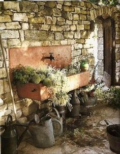This whole set up just puts me in another world.  I love the terra cotta colored sink along with the run down stone wall and galvanized watering pots.
