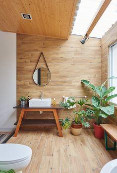 まるで屋外のように明るくて開放的な天窓と緑のある板張りのバスルームの洗面コーナー
