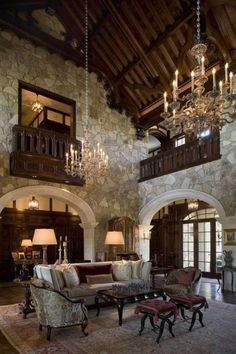 Home Design and Decor , Tudor Style Homes Interior : Tudor Style Homes With High Ceiling And Double Chandeliers And Stone Walls And Archway And  Couch And Side Chairs And Coffee Table And Benches