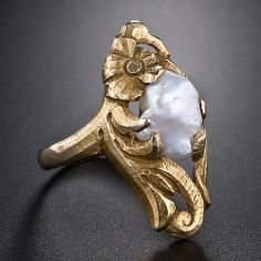 A shining and shimmering baroque freshwater pearl is enwrapped in elegantly sculpted flora in this thoroughly charming, nature-inspired Art Nouveau ring, circa 1900. $950
