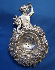 vintage sterling silver tea strainer with bunch of grapes design around the bowl, figure of satyr (Bacchus or Dionysus?) as handle