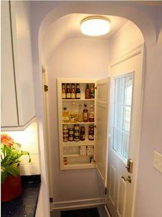 Between studs storage with little door - top of basement steps