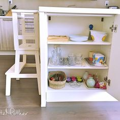 Montessori kitchen with tools and dishes on low shelves and learning tower.