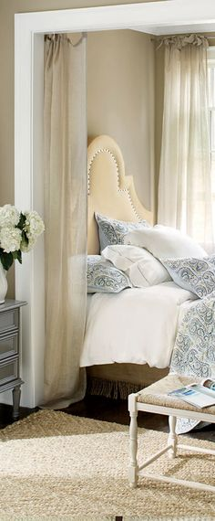 A wall niche creates a cozy space for this guest bedroom.  Sheer panels enhance the cocoon-like effect.