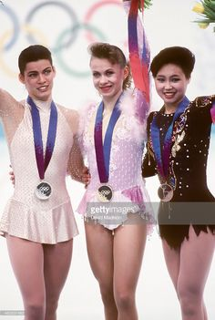 Nancy Kerrigan (USA) (left), Oksana Baiul (UKR) (center), and Lu Chen (CHN) (right) wave to the crowd at the medals ceremony for the Women's Figure Skating singles competition of the 1994 Winter Olympic Games on February 25, 1994 at the Hamar Olympic Amphitheatre in Lillehammer, Norway. Photo by David Madison/Getty Images)