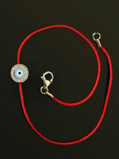 Aaron Basha 18KT White Gold and Pave Set Diamond Frame Evil Eye Bracelet on a Red Cord. Available at London Jewelers.