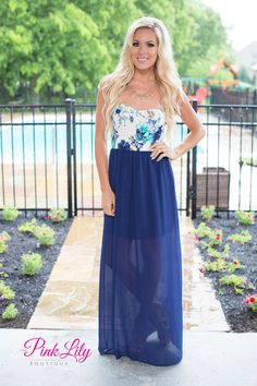 This new floral maxi is a must for your spring wardrobe! It features a gorgeous floral print with shades of grey, blue, and teal on a white bodice paired with a flowing navy blue skirt. It also has a strapless sweetheart neckline and an elastic band around the bottom of the bust.