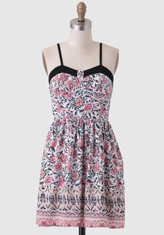 This breezy dress features an intricate rose, light-pink and black floral print  with black piping at the bust.