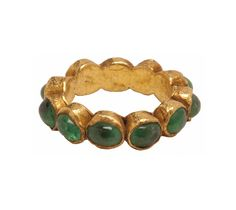 Eleven oval gold cells, each containing a highly polished cabochon emerald, were soldered together to form this ring. The emeralds are closely matched in color and clarity. Roman emeralds found in jewelry are typically cloudy and with many inclusions, and they were most often used in their natural crystal form rather than polished to a cabochon (convex) shape.