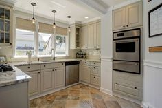 Traditional kitchen with antique white raised panel cabinets and slate floors