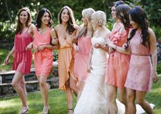 Bridesmaid dresses in different styles with toning colours of pinks and oranges.