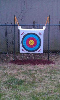 "DIY archery target holder. Use two wire fence posts, found in the outdoor fence section at Lowe's, hammer into ground at desired width. Use rope or plastic chain attached with caribiner to grommets on target and use ""S"" hooks to fasten to posts. Easy to take up and down. Am going to look for weather protective covering like patio furniture covering to keep from getting wet. All costs $10-15."