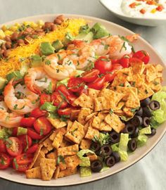Rainbow Mexican Salad with colorful and flavorful ingredients like tomatoes, Cheddar cheese, avocado, corn and olives are easily arranged to make a salad that gets a delicious crunch from crumbled cheese crisps. It makes a beautiful presentation and is ready in just 30 minutes.#CincoAvocados
