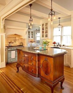 The centerpiece of the kitchen is an antique sideboard expanded at its back and topped with a granite counter top for an island work space. Lighting fixtures are French antiques from Bogart, Bremmer Bradley. (Benjamin Benschneider/The Seattle Times) Buffet Antique, Antique Sideboard, French Sideboard, Antique Dining Tables, Antique Glassware, Country Kitchen Designs, French Country Kitchens, Country Kitchen Lighting, Country French