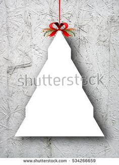 Blank tree shaped ornament frame hanged by clip with comet star and Christmas red ribbon against gray concrete wall background