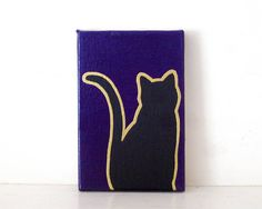 BLACK CAT Black Acrylic, Gold Embossing and Gloss Purple Enamel on Canvas Handmade in St. Louis, MO  You wont be afraid to cross paths with our black cat stalking your steps this Halloween! Welcome Trick-or-Treaters with this fun and festive Black Cat in your entry. Each hand-drawn, hand-painted canvas features a smart and spooky take on the classic Halloween theme. Featured here on a 4x6 Vampire Purple enamel canvas, Black Cat is also shown on 5x7 Pumpkin Orange and 6x8 Frankenstein Green…
