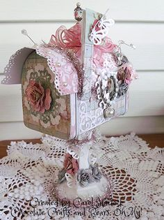 The beautiful shabby chic Primrose Stack from DCWV are the papers used in this project including the hand-made flowers. Spellbinders Bitsy Blossom was used to create the roses.  The vintage images are actually alter bottle caps that I made for this project. The tinsel is from Michael's that I picked up on sale