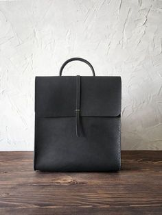 Women leather backpack. Minimalist bag. Handmade genuine leather rucksack. Black color. Cut, pierced and sewn by hand. Genuine leather 2 mm thick, waxed thread. Your initials or other information can be added with stamping method. SIZES: General W*H*D 270*310*75 mm (7.8*3.8*2.9 in) Pocket W*H 150*100 mm (5.9*3.9 in) Adjustable shoulder strap, 75 сm (29.5 in) (other length on demand). TREATMENT: with colourless leather cream or colourless spray. The colour will darken a bit with time in...