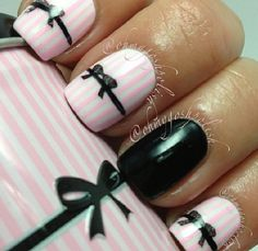 Pink and white stripped nails with black accent nail and black bows