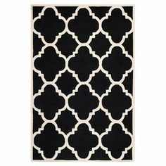 Hand-tufted wool rug with a quatrefoil motif.  Product: RugConstruction Material: WoolColor: Black and ivoryFeatures: Hand-tufted Note: Please be aware that actual colors may vary from those shown on your screen. Accent rugs may also not show the entire pattern that the corresponding area rugs have.Cleaning and Care: Professional cleaning recommended