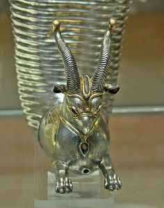 Protome of the gilt silver rhyton. The eye sockets were originally inlaid, as was the necklace with a gem, subsequently detached and missing. Punched dots cover the front of the head and the gilded cheeks. This rhyton was probably used to top up drinking bowls with wine during a banquet, hence the lowermost hole in the chest of the griffin. Possibly found at Altintepe, an ancient Urartian archeological site, Erzincan Province, Turkey. Achaemenid Persian Empire, 5th century BC