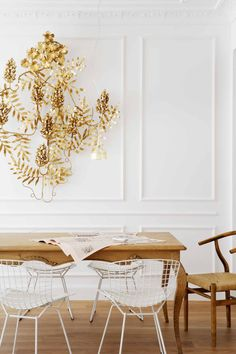 Ornate gold wall sculpture over modern dining table and Bertoia chairs