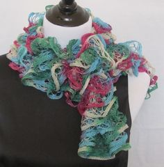 Christmas hand knitted ruffle scarf in jewel tones of magenta, green, blue and silver. Has silver thread thru out that makes it sparkle.