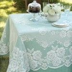 A lace tablecloth over a solid color tablecloth.