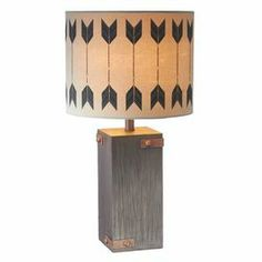 """Block-style table lamp with rivets, arrow accents, and a drum shade. For kait    Product: Table lampConstruction Material: Resin, fabric and metalColor: NaturalFeatures:   Charming designDistressed finish Accommodates: (1) 60 Watt bulb - not includedDimensions: 20.5"""" H x 12"""" Diameter"""