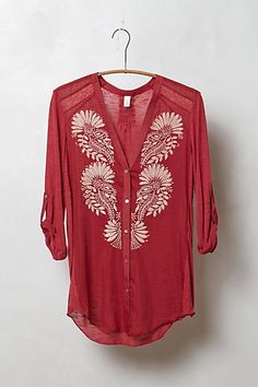 lovely muted red color, pretty embroidery, could be worn casually with shorts or classed up with skirt and heels.