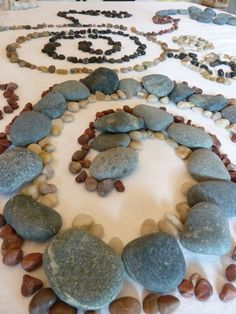 Playing with a variety of coloured stones in many sizes is a great open-ended activity.  When a white sheet is laid over table it provides a complementary contrast for the children to really see their work.
