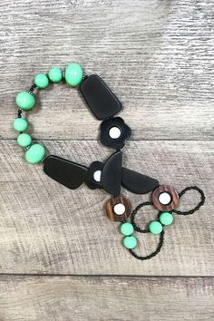 This chunky beaded necklace with aqua and black beads, touches of wood and white, it's the statement piece you need this summer.