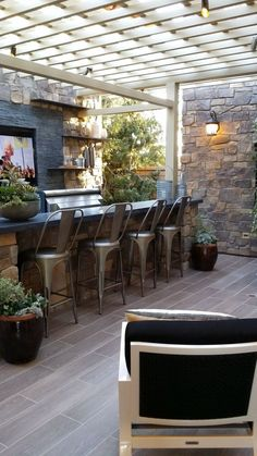 50 Stunning Outdoor Living Spaces - Style Estate - outdoor kitchen/bar space with TV.  I love the stone work and pergola. The lighting is fantastic.