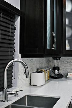 Marble backsplash works well with white quartz countertop and espresso cabinetry. I'd paint the walls a light gray instead
