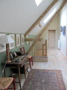Dans le couloir du second niveau, un mur de couleur vert amande (peinture Farrow and Ball) sculpte l'espace. Il contraste avec les montants des chaises en paille rouge cerise (peinture Farrow and Ball).