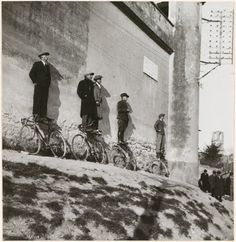 Men Standing on Bicycles Watching Game, 1934 by Fritz Henle