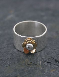 A handmade 10mm wide silver ring with a single brass daisy flower and silver bead in the centre.   #brass #daisy #flower #ring #jewellery #cornwall #uk #gb #westcountry #devon #england #silversmith #pretty #jeweller #jewellers #handmadejewellery