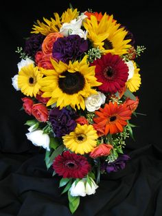 Cascade bouquet to a point created with yellow sunflowers, orange mini gerber daisies, yellow mini gerber daisies, burgundy mini gerber daisies, orange spray roses, ivory spray roses, and purple carnations.